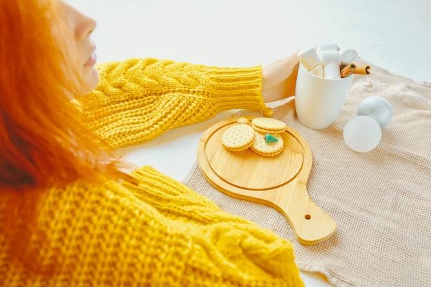 Piękno kobieta pije gorącą czekoladę z marsmallows i cynamonem w żółtym pulowerze