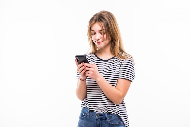 Piękno kobieta używa mądrze telefon odizolowywającego na białej ścianie i czyta