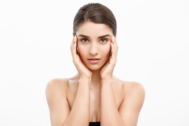 Piękno koncepcja pielęgnacji skóry piękna twarz kobiety rasy kaukaskiej portret piękny uroda młoda modelka dziewczyna dotyka jej twarzy skóra policzki ręce palce moda uroda model na białym tle