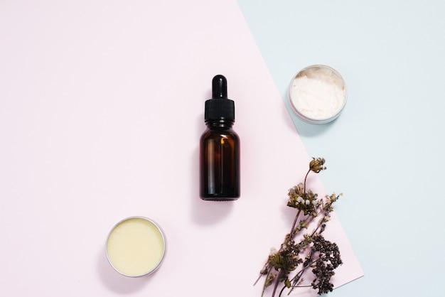 Piękno kosmetyk pielęgnacji skóry kremowe serum w tle. produkty z suszonych kwiatów, liści na blacie, płaskie układanie. minimalistycznie nowoczesny. bursztynowa butelka