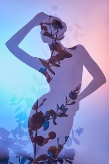 Piękno kwiaty ciało kobiety z podwójną ekspozycją. portret dziewczynki neonowe światło i kolor, profesjonalny makijaż, nagie plecy i tors kobiety, kwiaty w środku