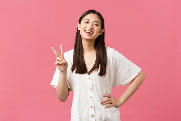 Piękno, ludzie emocje i koncepcja letniego wypoczynku. entuzjastyczna szczęśliwa japonka śmiejąca się i uśmiechająca, pokazująca znak pokoju kawaii w białej uroczej sukience, różowym tle