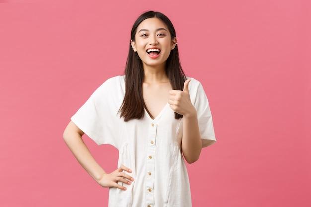 Piękno, ludzie emocje i koncepcja letniego wypoczynku i wakacji. radosna, zadowolona azjatycka klientka w sklepie, pokazująca kciuk w górę i śmiejąca się optymistycznie, polecająca miejsce odwiedzin, różowe tło