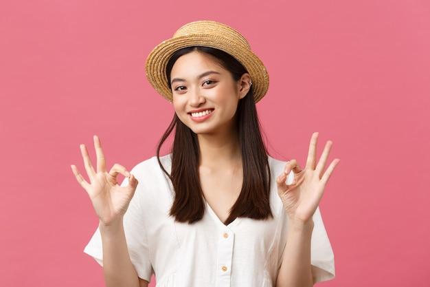 Piękno, ludzie emocje i koncepcja letniego wypoczynku i wakacji. uśmiechnięta szczęśliwa azjatka w słomkowym kapeluszu pokazując ok gest, polecam idealny hotel lub ośrodek turystyczny, stojąc na różowym tle.