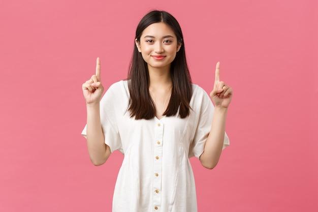 Piękno, ludzie emocje i koncepcja letniego wypoczynku i wakacji. uśmiechnięta urocza koreańska dziewczyna w białej sukience zapraszająca na wydarzenie, wskazująca palcami reklamę produktu, różowe tło