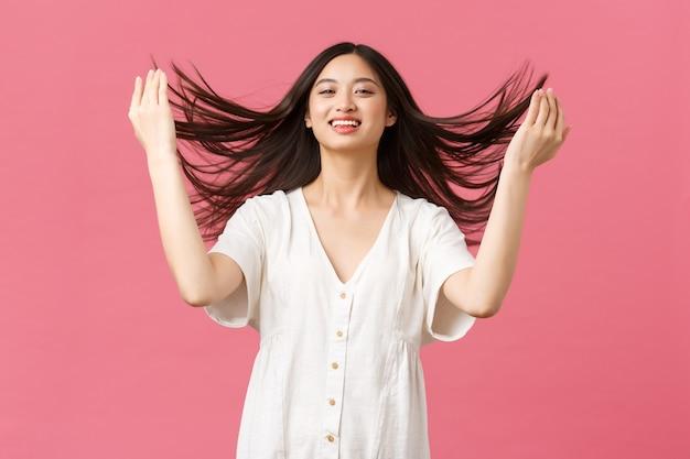 Piękno, ludzie emocje i koncepcja letniego wypoczynku i wakacji. zmysłowa i delikatna azjatka chwaląca się fryzurą, pokazywaniem włosów po produktach do pielęgnacji włosów lub salonie, różowe tło