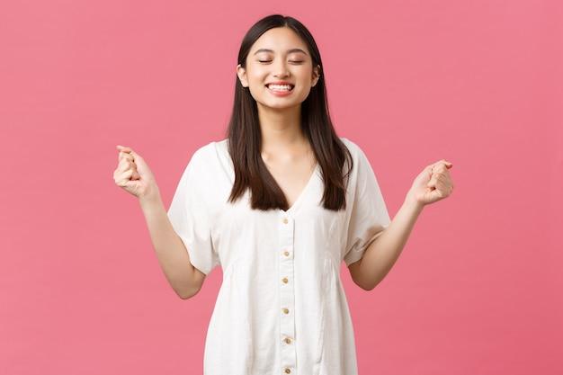 Piękno, ludzie emocje i koncepcja letniego wypoczynku. młoda pewna siebie śliczna azjatka uśmiechnięta optymistycznie, czująca siłę i entuzjastycznie, zachęcająca do zaciskania dłoni w pięści i uśmiechnięta z zamkniętymi oczami.