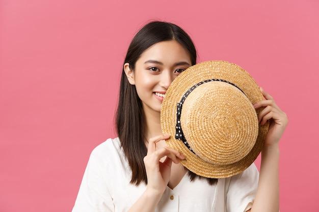 Piękno, ludzie emocje i koncepcja letniego wypoczynku. zbliżenie nieśmiałej i słodkiej japońskiej dziewczyny okładki twarzy za słomkowym kapeluszem i uśmiechniętego zmysłowego, stojącego różowego romantycznego tła.