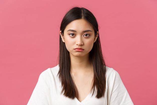 Piękno, ludzie emocje i koncepcja letniego wypoczynku. zbliżenie ponurej i smutnej, zmęczonej młodej azjatyckiej pracowniczki patrzącej na kamerę niechętnie, stojącej zmartwionej na różowym tle