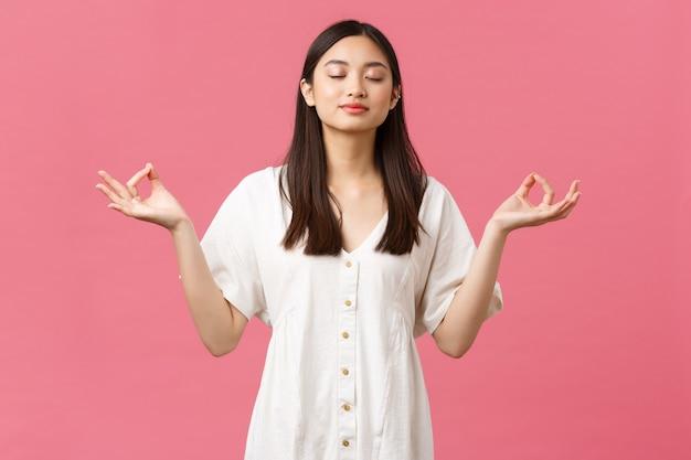 Piękno, ludzie emocje i koncepcja letniego wypoczynku. zrelaksowana i spokojna, zdeterminowana młoda azjatka medytuje w białej sukni, zamyka oczy i wykonuje ćwiczenia oddechowe jogi, różowe tło.