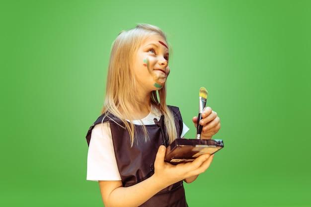 Piękno. mała dziewczynka marzy o zawodzie wizażystki. koncepcja dzieciństwa, planowania, edukacji i marzeń.
