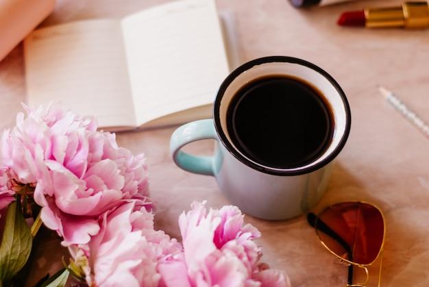 Piękno mieszkania leżał z pamiętnika, filiżankę kawy, akcesoria i piwonie na marmurowym tle