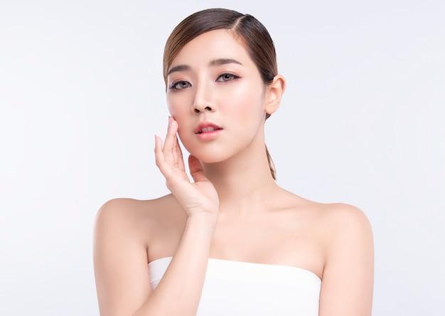 Piękno młoda azjatykcia kobieta z doskonałą skórą twarzy. gesty reklamy leczenia spa i kosmetologii.