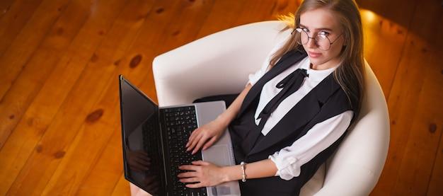 Piękno młoda kobieta jest usytuowanym w biurze z laptopem w szkłach.