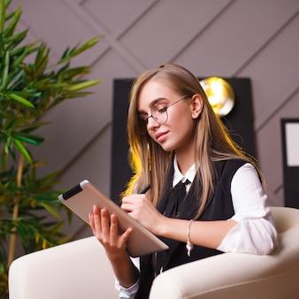 Piękno młoda kobieta jest usytuowanym w biurze z pastylką w szkłach