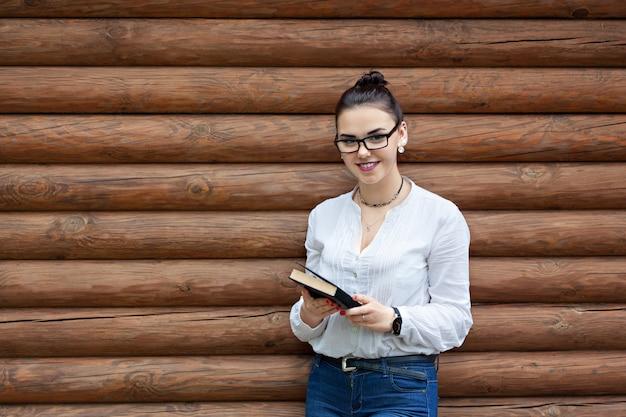 Piękno młoda kobieta w szkłach czyta książkę i uśmiech.