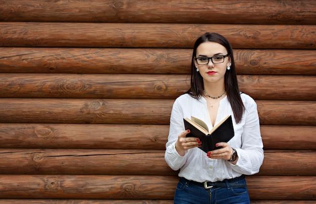 Piękno młoda kobieta w szkłach czyta książkę.