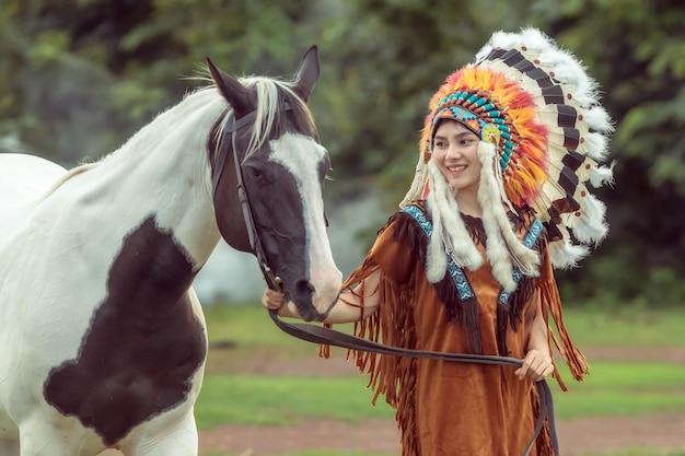 Piękno młodej azjatyckiej dziewczyny z makijażem jak pocahontas, czerwoną indianką i chodzeniem z american paint horse w ogrodzie w tajlandii