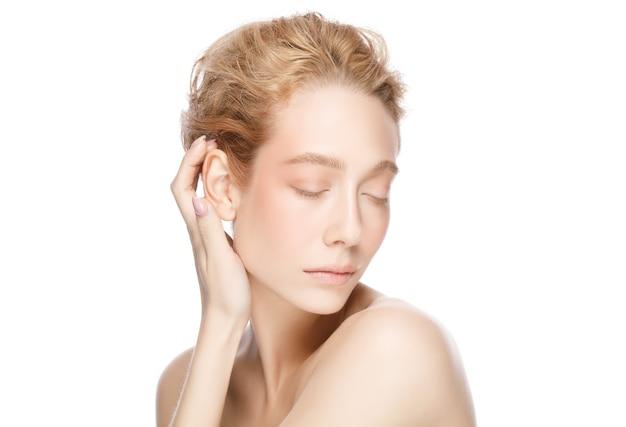 Piękno młodej pięknej blond kobiety z zamkniętymi oczami, dotykając jej idealnie czystej skóry