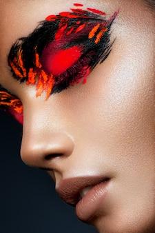 Piękno mody modela dziewczyna z ciemnym jaskrawym pomarańczowym makijażem