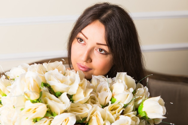 Piękno mody modela kobiety twarz. portret z kwiatami białej róży. piękna brunetka kobieta z luksusowym makijażem, idealna skóra. dzień walentyna