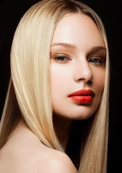Piękno mody modela portret z błyszczącą blondynki fryzurą z czerwonymi wargami na czarnym tle