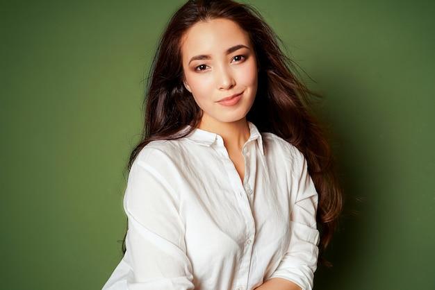 Piękno mody portret zmysłowa uśmiechnięta azjatykcia młoda kobieta z ciemnym długie włosy w białej koszula na zieleni