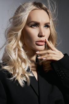 Piękno mody seksowna kobieta w kurtce i rajstopy, blondynki dziewczyna z długimi nogami. idealna figura modelki, portret kobiety na szarej ścianie