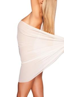 Piękno o gładkiej i zdrowej skórze. widok z boku pięknej młodej nagiej kobiety przykrywającej białym materiałem, stojąc na białym tle
