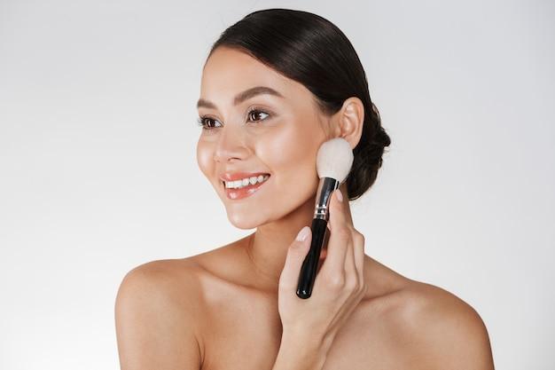 Piękno obrazek atrakcyjna kobieta patrzeje na boku i stosuje makeup z perfect uśmiechem używać muśnięcie, odizolowywającego nad bielem