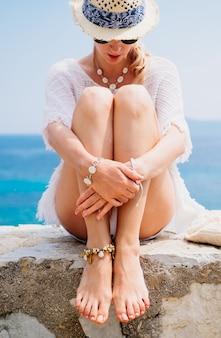Piękno opalona i stylowa młoda kobieta w białe ubrania, słomkowy kapelusz i okulary przeciwsłoneczne, siedząc nad morzem w słoneczny letni dzień