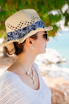 Piękno opalona i stylowa młoda kobieta w białych ubraniach, słomkowym kapeluszu i okularach przeciwsłonecznych stojąc nad morzem w słoneczny letni dzień i odwracając wzrok