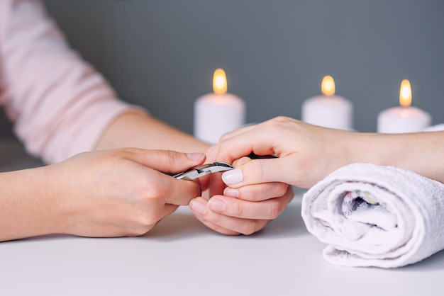 Piękno paznokci. kobieta ręce otrzymujące leczenie paznokci przez specjalistę manicure w salonie paznokci.