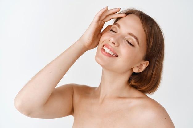 Piękno pielęgnacji skóry. naturalna dziewczyna o zdrowej, promiennej skórze, dotykająca nawilżonej twarzy i uśmiechająca się z zamkniętymi oczami. kobieta ciesząca się świeżym i czystym uczuciem po kosmetykach, biała ściana