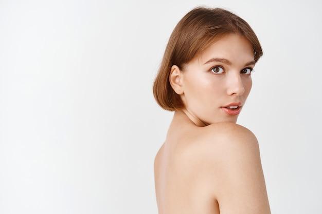 Piękno pielęgnacji skóry. piękna kobieta stojąca z nagimi ramionami, figlarnie patrząca z naturalną piękną twarzą, bez makijażu i odżywioną zdrową skórą twarzy, biała ściana