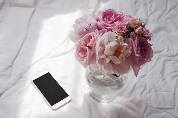 Piękno płaskie leżało z telefonem i kwiatem