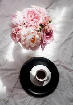 Piękno płasko leżało z kawą i bukietem kwiatów róż i pions