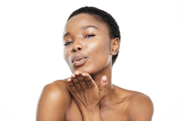 Piękno portret afro amerykańskiej kobiety dmuchanie pocałunkiem w aparacie na białym tle na białym tle