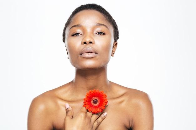 Piękno portret afro amerykańskiej kobiety pozującej z kwiatem na białym tle