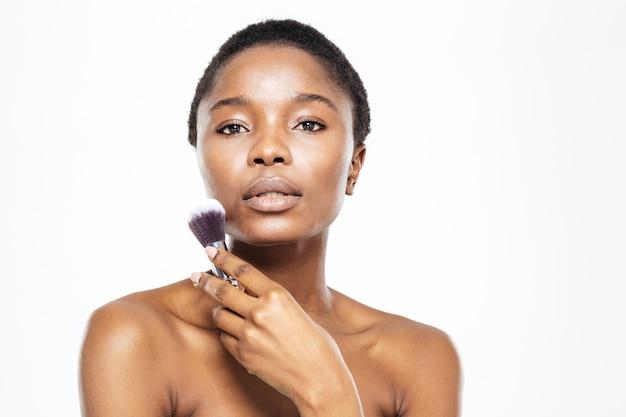 Piękno portret afro amerykańskiej kobiety trzymającej pędzel do makijażu na białym tle na białym tle