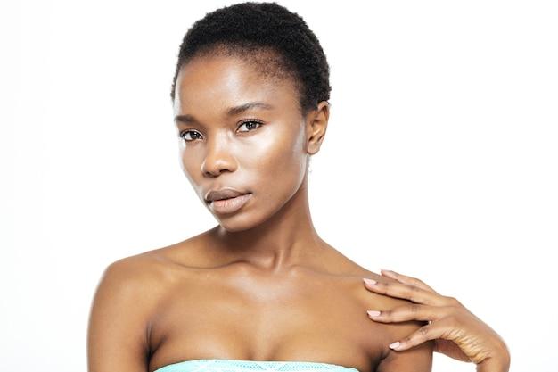 Piękno portret afro amerykańskiej kobiety z idealną skórą patrząc na kamerę na białym tle