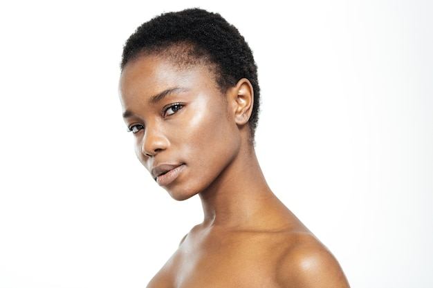 Piękno portret afro amerykańskiej kobiety ze świeżą skórą patrząc na kamerę na białym tle