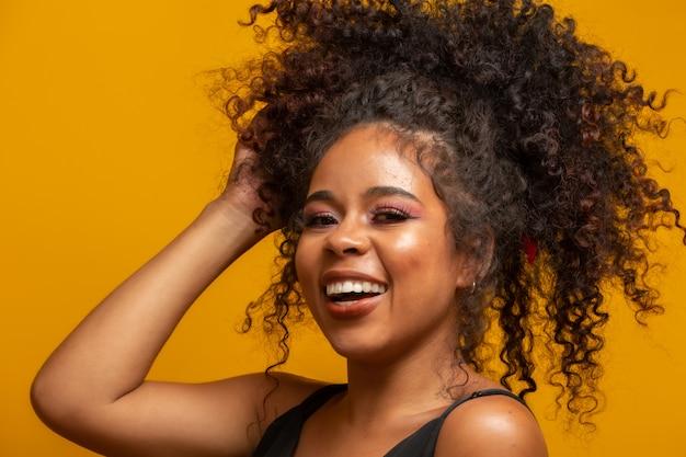 Piękno portret amerykanin afrykańskiego pochodzenia kobieta z afro fryzurą i splendoru makeup. brazylijka rasa mieszana. kręcone włosy. fryzura żółta ściana.