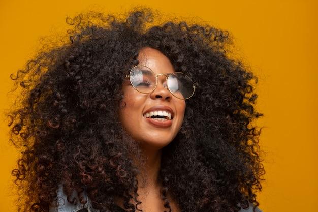 Piękno portret amerykanin afrykańskiego pochodzenia z szkłami i afro fryzurą na żółtej ścianie. brazylijska młoda kobieta.