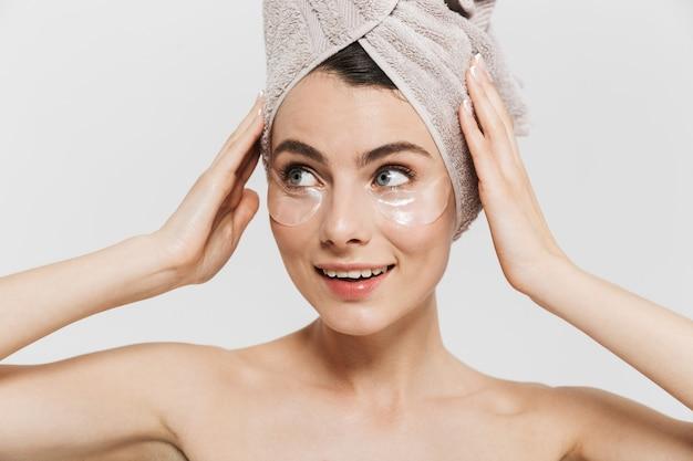 Piękno portret atrakcyjnej młodej brunetki kobiety stojącej na białym tle nad białą ścianą, noszącej ręcznik na głowie, nakładającej kosmetyczne plastry na oczy