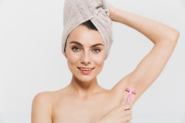 Piękno portret atrakcyjnej młodej brunetki stojącej na białym tle nad białą ścianą, noszącej ręcznik na głowie, golącej się pod pachami