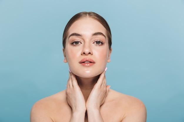 Piękno portret atrakcyjnej młodej kobiety topless na białym tle nad niebieską ścianą, pozowanie