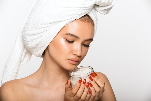 Piękno portret atrakcyjnej młodej kobiety topless noszenia ręcznika łazienkowego na głowie stojącego na białym tle nad białą ścianą, trzymając słoik z solą morską