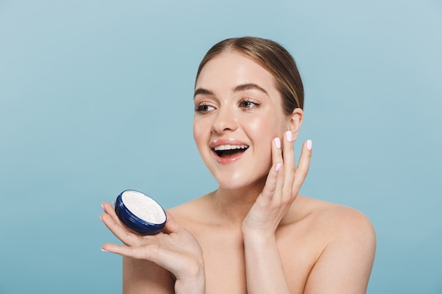 Piękno portret atrakcyjnej młodej kobiety topless odizolowanej na niebieskiej ścianie, nakładającej krem z pojemnika