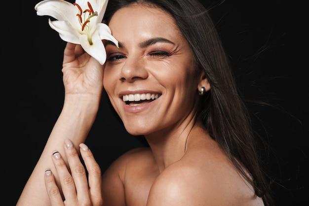 Piękno portret atrakcyjnej młodej kobiety topless z długimi brunetkowymi włosami odizolowanej na czarnej ścianie, pozującej z kwiatem orchidei